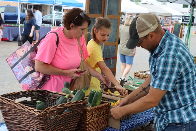 Lesli and Angel Bashaw pick a variety of squash from Blaine Burnett at the Canyon Farmers' Market that runs from June 26, 2021 through September 25, 2021 around the Courthouse Square in Canyon, Texas.