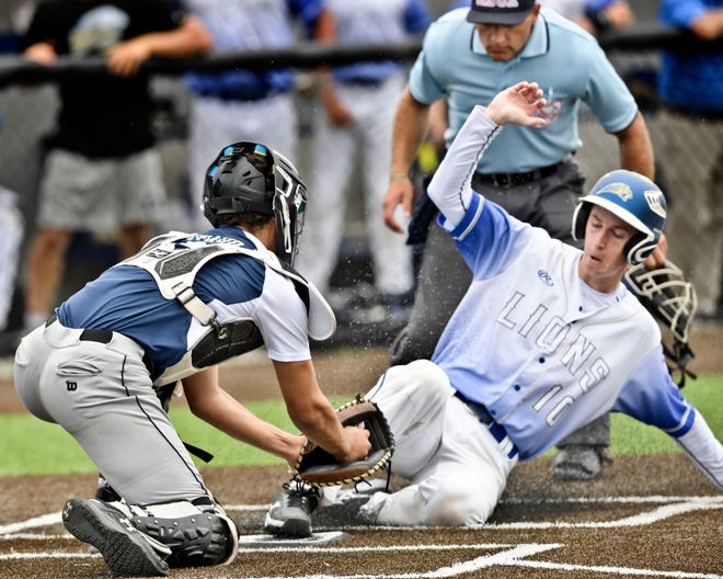 Jacob Lenau of St. John Paul II arrives safely at home ahead of the tag by Cohasset catcher Luc Nivaud in Friday's thriller.