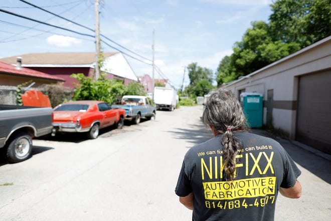 Nick Sewell walks around NikFixx Automotive and Fabrication in Columbus, Ohio on June 23, 2021. Nick has overcome a troubled past and now runs a repair shop and three sober houses in Columbus.