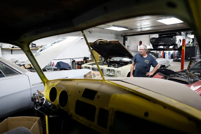Nick Sewell shows off some cars inside NikFixx Automotive and Fabrication on the South Side. Sewell has overcome a troubled past and now runs a repair shop and three sober houses in Columbus to help give others a leg up.