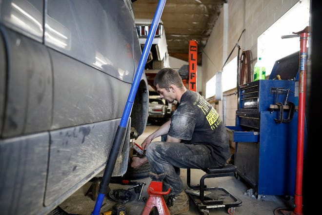 Jesse Eldridge works on fixing brakes on an Amazon Prime van at NikFixx Automotive and Fabrication in Columbus, Ohio on June 23, 2021. Owner Nick Sewell has overcome a troubled past and now runs a repair shop and three sober houses in Columbus.  Jesse works at the shop and also stays at one of the three sober houses.