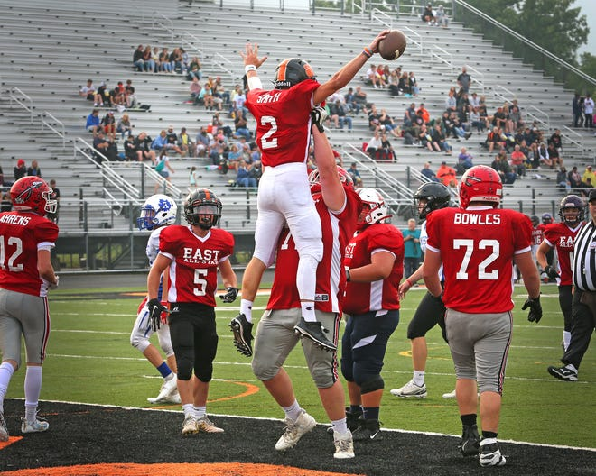 Clinton's Will Felts lifts up Hudson's Dylan Smith after Smith scores a touchdown for the East team in Friday's Lenawee County Senior Showcase All-Star Football Game at Tecumseh High School.