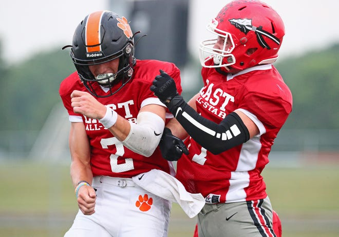 East All-Stars Dylan Smith (Hudson, left) and Davey Campbell (Clinton) celebrate after Smith connected with Campbell for a touchdown pass in Friday's Lenawee County Senior Showcase All-Star Football Game at Tecumseh.