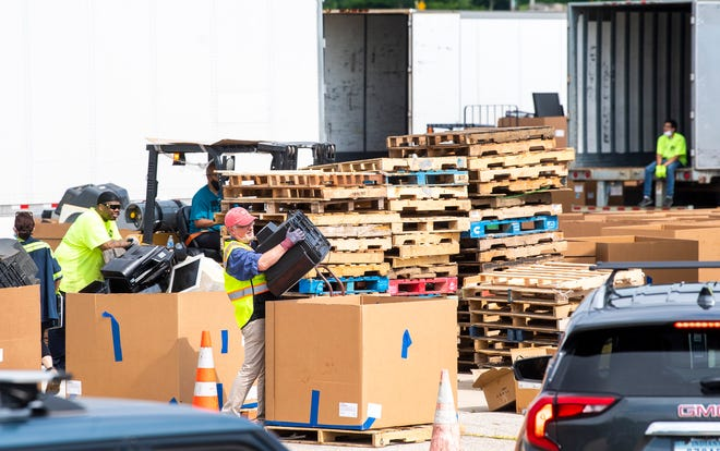 Employees of Cook Inc. and Big Boy Moving Services load discarded electronics into large cardboard bins Saturday during the Community Electronic Recycling Day at the Cook Profile Park facility.