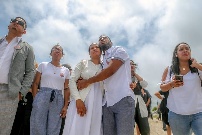 Carla Martinez, mother of YoskarlyMartinez, and her brother Carlos Martinez embrace after releasing two white doves at the site of Yoskarly's drowning last weekend at Conimicut Point in Warwick.
