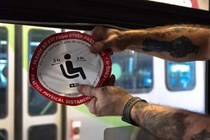 A Lane Transit District team member works to remove social-distancing reminders from a bus. Gov. Kate Brown lifted the remaining COVID-19 health and safety restrictions in Oregon, effective Wednesday.