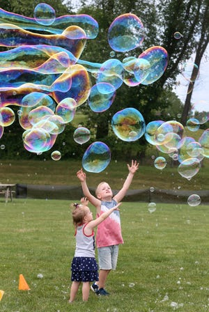 Emma and brother Sam VanDyke chase bubbles Saturday during FreedomFest at Boettler Park in Green.