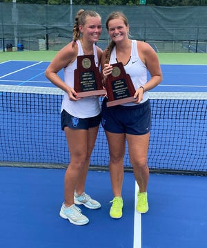 Macy Morrison (left) and Elizabeth Vollmin pose with the trophies after winning the NCHSAA 4A Girls Tennis doubles state championship Saturday afternoon.