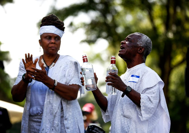"""Ayoka Sowa-La, left, and Nii """"PaPa"""" Sowa-La, right, conduct a libation ceremony during the Alachua-Newnansville Community Remembrance Project Soil Collection Ceremony at A. L. Mebane Middle School on Saturday in Alachua. [Chasity Maynard/Special to The Sun]"""