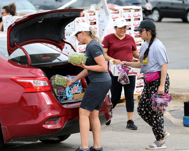 Volunteers, from left, Kelly Davis, Sandra Hernandez and Anna Dang load fresh fruit at the distribution line for the Antioch for Youth & Family Child Summer Feeding Program in Fort Smith, Ark.