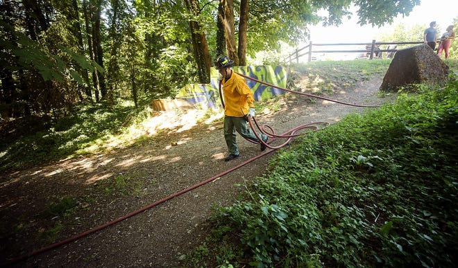 Bremerton Fire's Cody Hoefs pulls hose from the parking lot to the scene of a small brush fire at the trailhead of Stephenson Canyon in Bremerton on June 26.