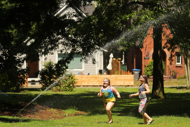 Charlie Blackwell, 8, and her sister Rylie, 9, cool off by running through one of the sprinklers at Bremerton's Evergreen Rotary Park on a hot Saturday.