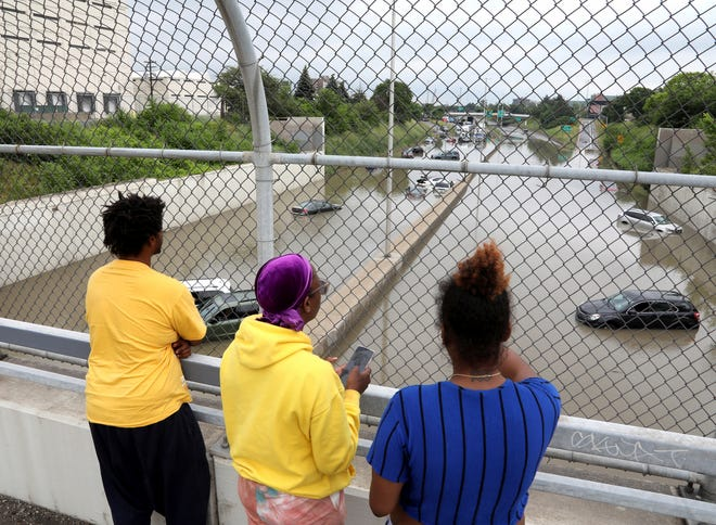 People standing on Rosa Parks over I-94 watch and talk about all the cars and trucks stuck and stalled on I-94 West and Eastbound in Detroit on June 26, 2021. Heavy rains in Metro Detroit caused massive flooding in homes, streets and freeways.