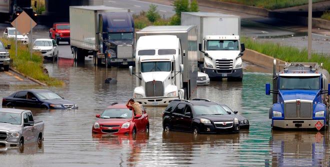 Un hombre en un SUV rojo rodeado por otros autos y camiones también varados y varados espera ayuda en la I-94 West cerca de Trumbull y Rosa Parks en Detroit el 26 de junio de 2021. Las fuertes lluvias en el área metropolitana de Detroit han causado inundaciones masivas en hogares. calles y carreteras.