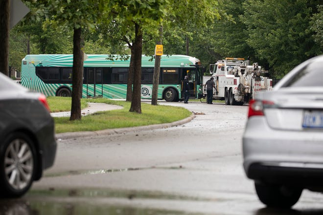 Workers try to assess how to move a Detroit bus that became stuck in floodwaters on Dickerson in Detroit, June 26, 2021. Heavy rains in Metro Detroit caused massive flooding in homes, streets and freeways.