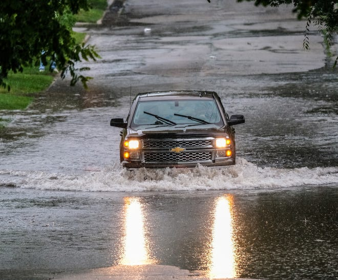 A truck moves carefully through standing water on a Lansing street after a deluge Saturday, June 26, 2021. The Lansing area had several tornado warnings late in the afternoon with heavy rain.