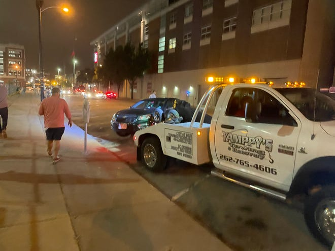 A tow truck is parked near the temporarily expanded no-parking zone on Water Street downtown. Expansion of that zone is one way Milwaukee leaders are trying to respond to recent unrest in the downtown district.