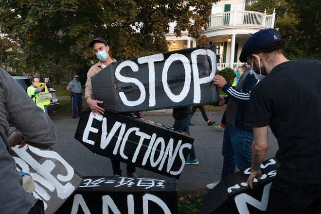 FILE - In this Oct. 14, 2020, file photo, housing activists erect a sign in Swampscott, Mass. A federal freeze on most evictions is set to expire soon. The moratorium, put in place by the Centers for Disease Control and Prevention in September, was the only tool keeping millions of tenants in their homes. (AP Photo/Michael Dwyer, File)