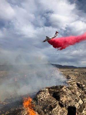 An airplane drops water on a fire in the Virgin River Gorge after fire crews had been working to contain the wildfire all day, June 25, 2021.