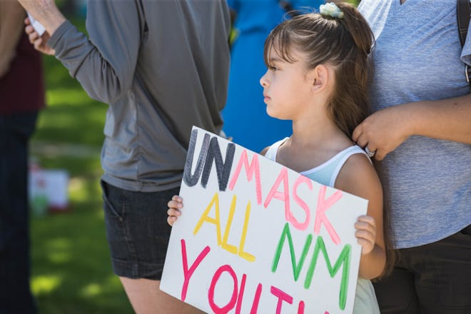 A child stands among those asking for the state to lift mask restrictions for youth on June 26.