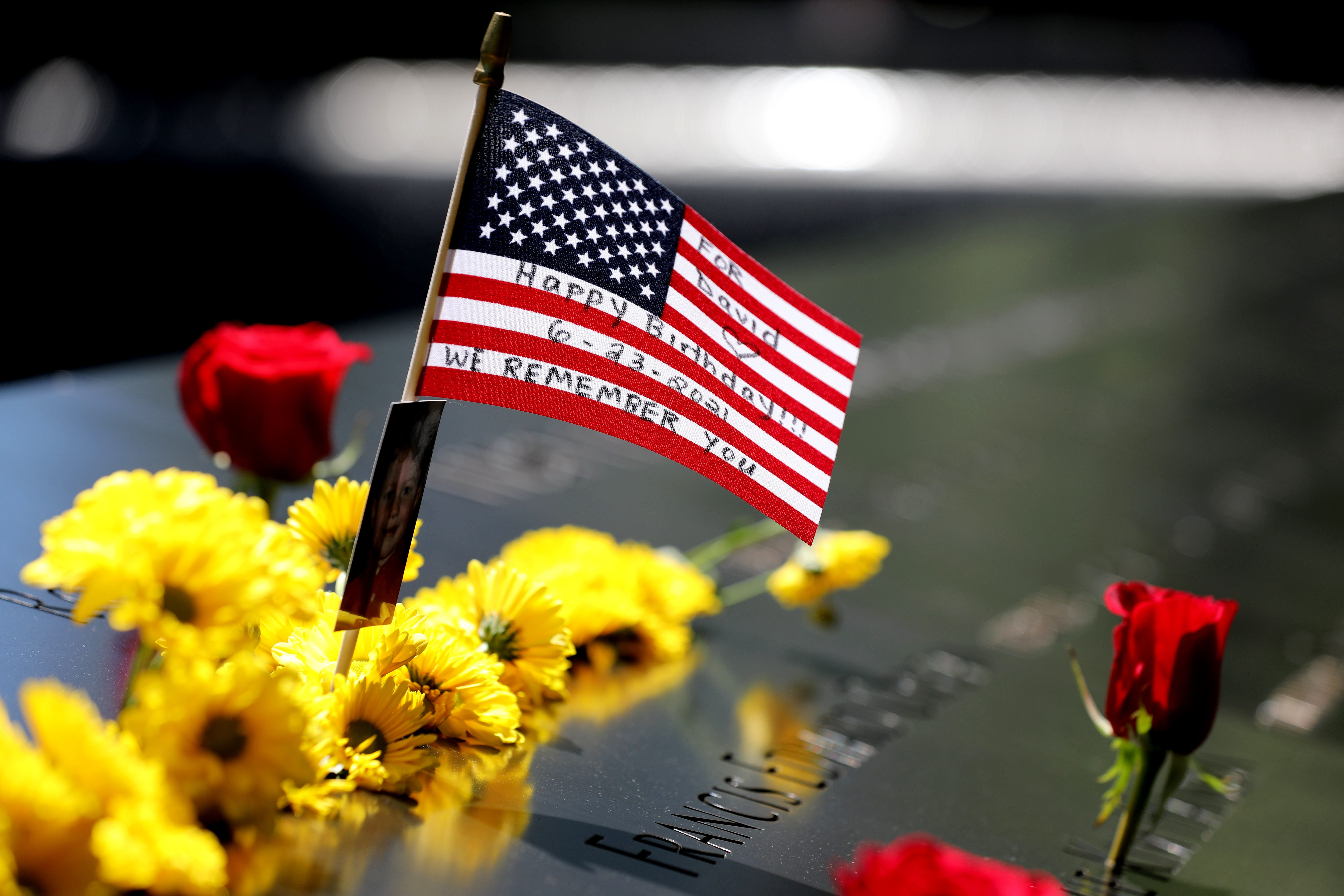 A small American flag with a note remembering a victim of the Sept. 11 attacks is left at the 9/11 Memorial at the World Trade Center in Manhattan on June 24, 2021.