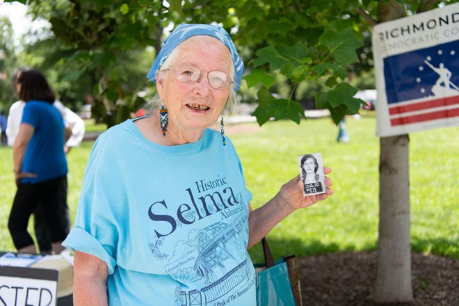 Joan Trumpauer Mulholland, who participated in the Freedom Rides in 1961, holds up a copy of her mugshot from when she was arrested in Jackson, Miss. The civil rights veteran was a speaker at a rally June 25, 2021, at Monroe Park in Richmond, Va., hosted by Black Voters Matter commemorating the 60th anniversary of the Freedom Rides.