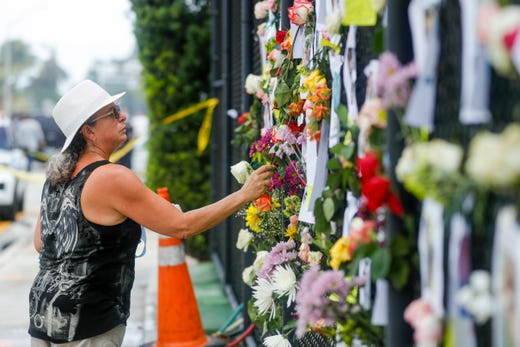 Nora Estevez adds a rose to a make-shift memorial near the site where a 12-story building partially collapsed in the community of Surfside, Florida on June 26, 2021.