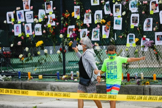 A woman holding hands with a kid walk by the site of a make-shift memorial for people to gather and pray for the people missing after a 12-story building partially collapsed in the community of Surfside, Florida on June 26, 2021.