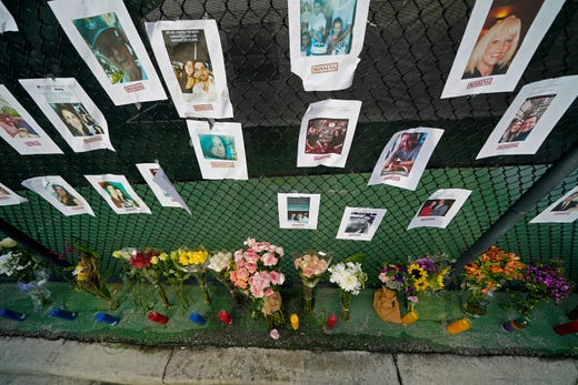 A makeshift memorial bears photos of some of the missing people that hangs from a fence, near the site of an oceanfront condo building that partially collapsed in Surfside, Fla., Friday, June 25, 2021.