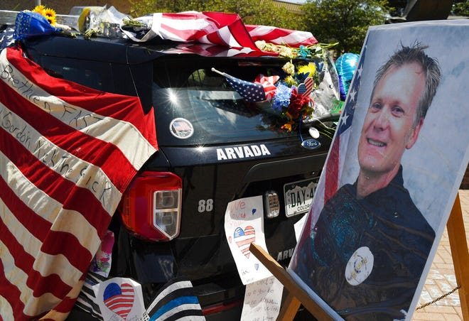 Flowers, flags and notes cover a patrol car and bike outside Arvada City Hall during a memorial for Arvada Police Officer Gordon Beesley on Tuesday.