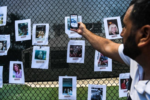 A man uses his phone as he looks at pictures of missing residents of the partially collapsed building at a makeshift memorial in Surfside, north of Miami Beach, on June 25, 2021.