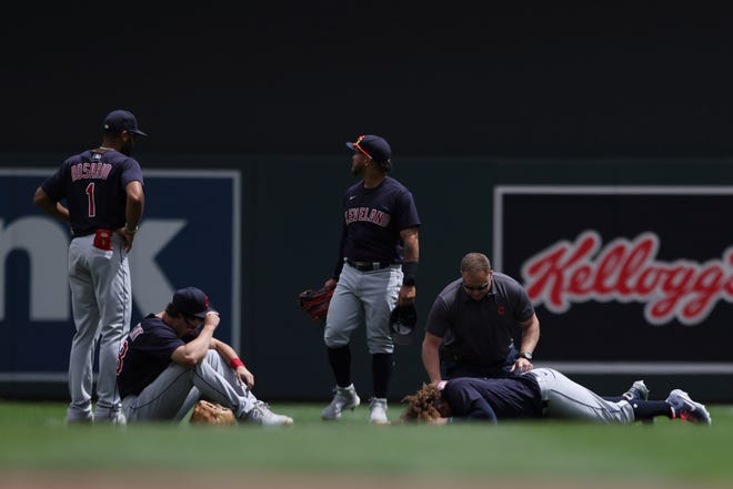 Cleveland's Josh Naylor lies on the ground after colliding with teammate Ernie Clement (seated left) on Sunday.