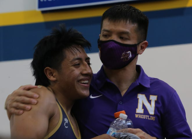 North Henderson's Lazaro Vasquez and coach Heang Uy share a special moment after Vasquez wrapped up his prep career with a fourth-place finish at the 3-A championship on Saturday in Gibsonville. [DEAN HENSLEY/ TIMES-NEWS]