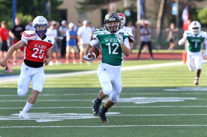 West's Ty Sides (12) from Phillipsburg runs down the field away from East's Thad Metcalfe (25) from Perry-Lecompton during the 2021 Kansas Shrine Bowl game at Gowans Stadium in Hutchinson Saturday night. West squad defeated East 14-0. Sides was named the most valuable player for the West squad.