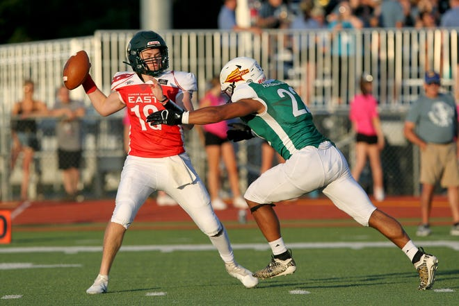 East's quarterback Isaac Stanton (18) from Basehor-Linwood is tackled by West's Gaven Haselhorst (22) from Hays during the 2021 Kansas Shrine Bowl game at Gowans Stadium in Hutchinson Saturday night. The West squad defeated the East squad 14-0.