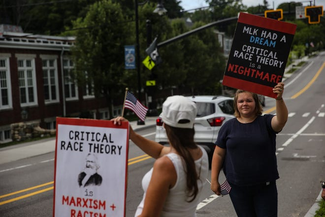 Laura Rymer, president of Medway for All, holds a sign during a rally sponsored by the group opposing the teaching of critical race theory in schools at Choate Park in Medway, June 26, 2021.