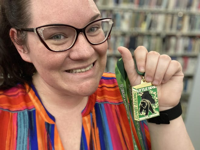 Little Dixie Regional Libraries librarian Taylor Bequette with 2021 Summer reading medal.