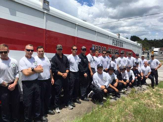 Members of Florida's Urban Search and Rescue Task Force 8 pose at a staging area Sunday as they prepare to deploy to the Champlain Towers South condominium collapse site in Surfside. The task force is comprised of first responders from Marion County Fire Rescue, Ocala Fire Rescue and Gainesville Fire Rescue.