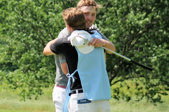 Ryan Quinn gets a big hug from caddie Eric Evans on the 18th green after Quinn won the 41st annual Seacoast Am by nine shots after Sunday's third round at Portsmouth Country Club. [Al Pike photo]