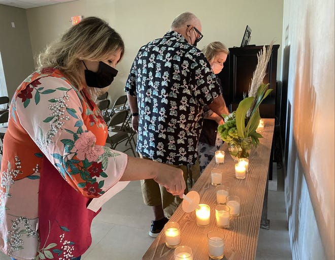 At the back of the church office chapel, worshippers set a flame to the unlit candles that dotted a wooden table.