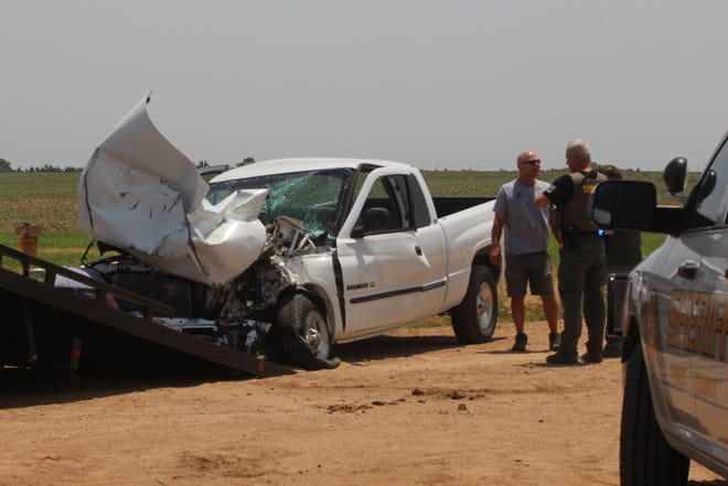 A Pratt County Sheriff's Deputy and local residents evaluate a Dodge pickup as it is readied for removal from the scene of an accident that happened Thursday just after noon last week north of Pratt. A teenage driver in the pickup ran into the back axle of a semi hauling a full load of corn.