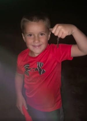 Kacin Strong holds up a nightcrawler he found at Lemon Park last week, after a significant rainfall brought the large worms up to ground-surface.