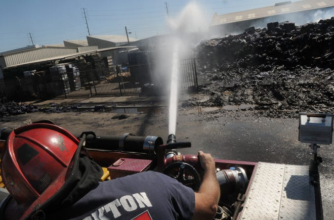 Stockton Fire Capt. Tony Moudkis shoots water onto a smoldering fire at M. Calosso & Sons on July 5, 2013, that was ignited by neighborhood fireworks