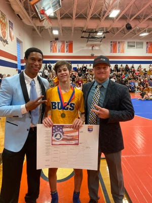 Laney's Mark Samuel (middle) poses with head coach Andre Adams (left) and assistant coach Leonard Harrison after winning the NCHSAA 4A 120-pound weight class state championship.