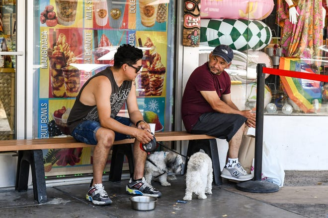 Odin Vega and Jose Garcia from Los Angeles give their dogs Nikki and Roko water at Lappert's Ice Cream in Palm Springs on Sunday, June 27, 2021.