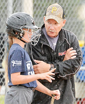 Watertown Raging Thunder coach Bob Reiter visits with Ashlynn Vavruska during a 12-and-under division game over the weekend in the Watertown Fastpitch Softball Association's Premier Throwdown tournament.