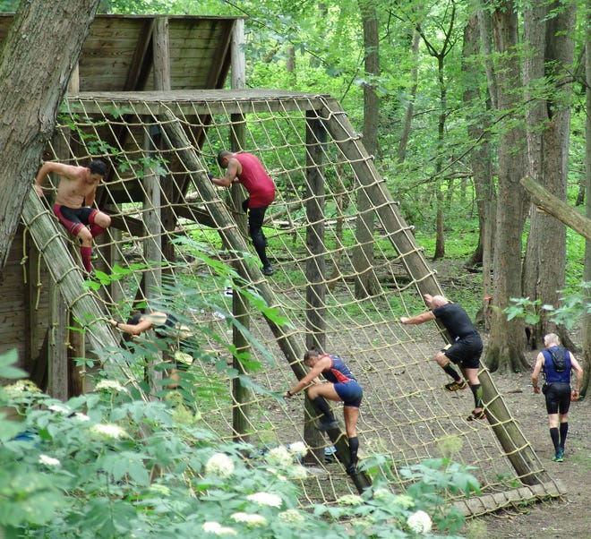 Participants in the 2021 Indian Mud Run at Lake Park on Ohio 83 climb down on the more than 80 obstacles that dotted the 6.6 mile course.
