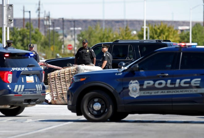 The basket of the fatal balloon crash is seen lying on the pavement as police officers inspect the area in Albuquerque, N.M., Saturday, June 26, 2021.  Multiple people were killed in the crash.