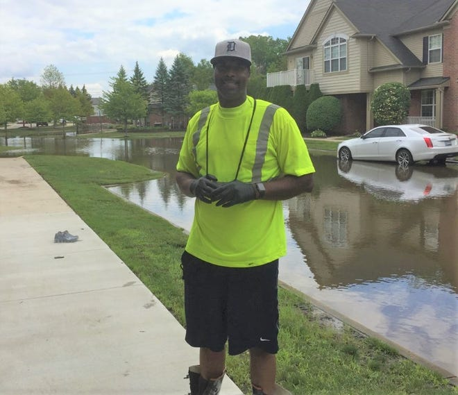 As flood waters submerged the streets of Canton's Woodlands of Chatterton Village condominium development, James Garth retrieved a pump and spent more than 10 hours helping remove water from his neighborhood.