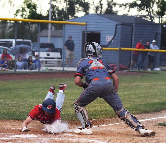 Ballard's Nolan Schnhorst slides safely into home plate during the Bombers' 6-1 victory over Ames in six innings June 22 at Nite Hawk Field in Slater.